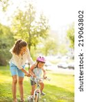 mother helping baby girl riding ... | Shutterstock . vector #219063802