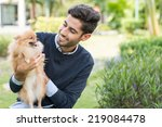 Stock photo smiling man looking at pomeranian spitz in his hands 219084478