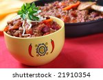 Bowl of chili with beans, with cooking pan behind.  Delicious chili con carne. - stock photo