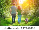 Stock photo young couple holding hands and walking with their dog in the forest 219444898