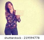 doubtful girl holding a name... | Shutterstock . vector #219594778