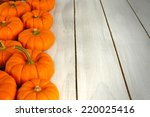 Autumn pumpkins forming a border against white wood - stock photo