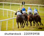 Stock photo jockeys and horses racing down the track view from behind 220593958