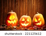 Stock photo jack o lanterns halloween pumpkin face on wooden background and autumn leafs 221125612