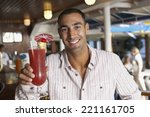 hispanic man holding cocktail | Shutterstock . vector #221161705
