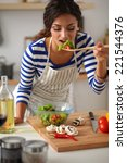 young woman eating fresh salad... | Shutterstock . vector #221544376
