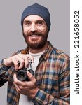 Confident photographer. Handsome young bearded man holding old-fashioned camera and smiling while standing against grey background