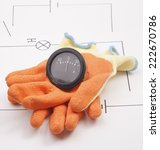 Small photo of Ammeter and mounting gloves on a background of the electric scheme