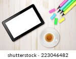 Empty tablet and a cup of coffee on the wooden desk - stock photo