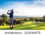 Man Hitting Golf Ball Down Hill ...