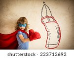 Small photo of Superhero kid in red boxing gloves. Child punching on the drawn bag. Winner and success concept