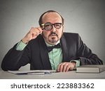 Small photo of Curious corporate businessman skeptically looking at you through magnifying glass sitting at desk isolated on office grey wall background. Human face expression, body language, attitude, body language