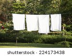 Stock photo fresh clean white towels drying on washing line in outdoor 224173438