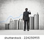 Young professional drawing a growing real estate chart. Concrete background.  - stock photo
