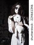 Small photo of Horror style shot: a strange crazy girl with moppet doll and needle in hands