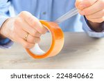 Small photo of Hands with roll of transparent packaging, adhesive tape.