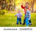 happy kids blow bubbles outdoors | Shutterstock . vector #226083922