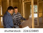 Two builders inside a half completed timber frame house standing having a discussion over a blueprint of the building - stock photo