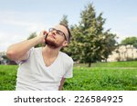 bearded man sitting in park on... | Shutterstock . vector #226584925