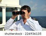 Small photo of navigator on navigation bridge during his watch on seagoing vessel with binocular