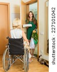 Small photo of Old woman in wheelchair meeting girl with foodstuff at threshold