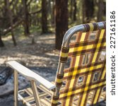 Retro fold up camping chair in front of the fire in the woods - stock photo