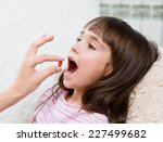 child receiving pill   closeup | Shutterstock . vector #227499682
