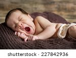 Cute Newborn Yawns Lying On...