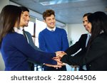 smiling co workers making pile... | Shutterstock . vector #228044506