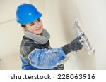 Small photo of female plasterer painter at indoor wall renovation decoration stopping with spatula and plaster