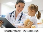 doctor examining a child in a... | Shutterstock . vector #228381355