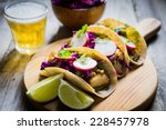 fish tacoes on wooden background | Shutterstock . vector #228457978