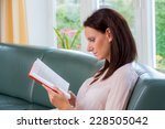 Small photo of a young woman sitting on a couch and reading a book