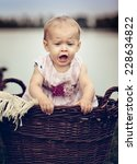 Portrait of a small baby girl at a Lake in Wicker Basket - stock photo
