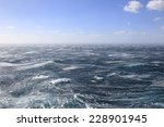With Blue sky Fierce winds whip up the sea - stock photo
