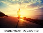 Stock photo runner athlete running at seaside woman fitness silhouette sunrise jogging workout wellness 229329712