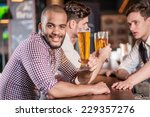 man holding a glass of beer in... | Shutterstock . vector #229357276