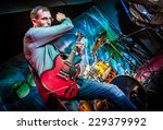 Band performs on stage, rock music concert. Warning - Focus on the drum! - stock photo