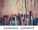 Stock photo row of artist paintbrushes closeup on old wooden rustic table retro stylized 229530475