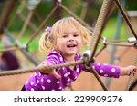 Happy Little Girl Climbing On...