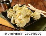 A plate of Chinese chicken dumplings with soy sauce and chop sticks