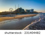 View of hotels and rides along the boardwalk from the fishing pier in Daytona Beach, Florida.