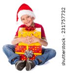 happy boy in Santa hat with yellow Christmas gift box, isolated on white - stock photo