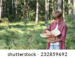 Teenage boy tasting fresh forest red wildberries