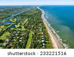 Small photo of aerial view looking north, of Jupiter and Hobe Sound, Florida, along the Atlantic Ocean coast, lined by the beach and dotted by luxury homes golf courses