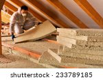 Man installing thermal insulation layer under the roof - using mineral wool panels - stock photo