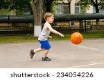 Little Boy Playing Basketball...