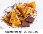 crepes with chocolate and dessert spoon on white table - stock photo