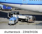 Loading an airplane with airfreight at an airport - stock photo