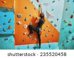 Young Woman Climbing Up On...